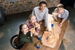 Vrienden die tijd samen met pizza en sodadranken doorbrengen, die pizza thuis concept eten Royalty-vrije Stock Foto