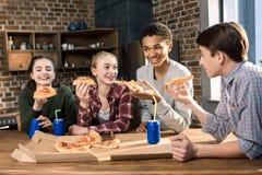 Vrienden die tijd samen met pizza en sodadranken doorbrengen, die pizza thuis concept eten Stock Afbeeldingen