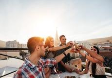 Vrienden die uit met dranken op dakpartij hangen royalty-vrije stock afbeeldingen