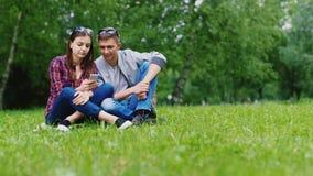 Vrienden die van een man en een vrouw die van slimme telefoon genieten, op het gras in het park zitten stock videobeelden