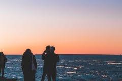 Vrienden die van een zonsondergang genieten door het overzees royalty-vrije stock fotografie