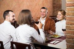 Vrienden die van heerlijke maaltijd in het restaurant van het land genieten Stock Afbeelding