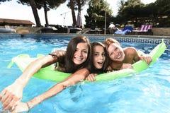 Vrienden die van het trio de gelukkige en mooie jonge meisje knuppel hebben Stock Afbeeldingen