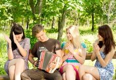 Vrienden die van muziek genieten die op een concertina wordt gespeeld stock fotografie