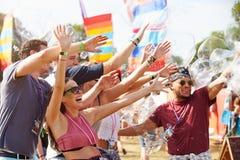 Vrienden die van prestaties genieten bij een muziekfestival stock fotografie