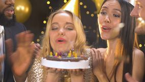 Vrienden die verjaardag vieren en handen, dame blazende kaarsen op cake slaan stock videobeelden
