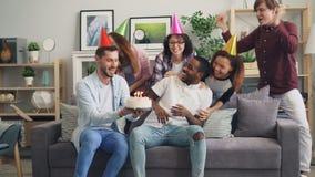 Vrienden die verrassings brengende cake op verjaardag maken aan droevige Afrikaanse Amerikaanse kerel stock video