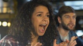Vrienden die vingers voor goed geluk kruisen, die voor de overwinning van het sportenteam in bar toejuichen stock footage