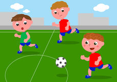 Vrienden die voetbal op voetbalgebied spelen Stock Foto's