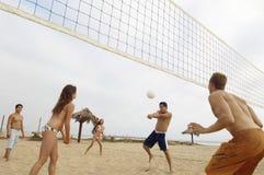 Vrienden die Volleyball op Strand spelen Stock Afbeelding