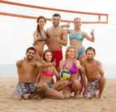 Vrienden die volleyball spelen bij strand Stock Afbeeldingen