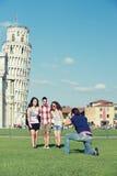 Vrienden die whit van de Foto de Leunende Toren van Pisa nemen stock foto's