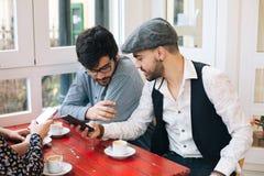 Vrienden in een bar die mobiles gebruiken royalty-vrije stock foto's