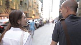 Vrienden, een man en een vrouw die, die langs een bezige straat in het stadscentrum lopen en, het glimlachen spreken De mening va stock video