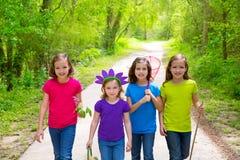 Vrienden en van zustermeisjes lopen openlucht in bosspoor Stock Foto