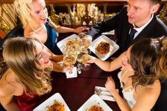 Vrienden in glazen van een de zeer goede restaurantgerinkel Stock Afbeeldingen