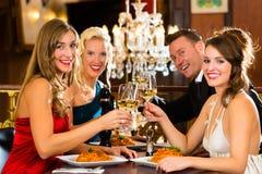 Vrienden in glazen van een de zeer goede restaurantgerinkel Stock Fotografie