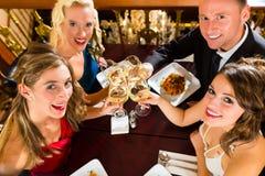 Vrienden in glazen van een de zeer goede restaurantgerinkel Stock Foto's