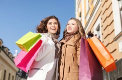 Vrienden het winkelen. Lage hoekmening van gelukkige twee jonge vrouwenstandi Royalty-vrije Stock Foto's