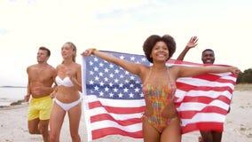 Vrienden met Amerikaanse vlag die op de zomerstrand lopen stock footage
