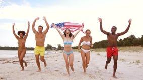 Vrienden met Amerikaanse vlag die op de zomerstrand lopen stock video