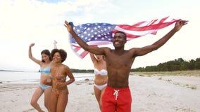 Vrienden met Amerikaanse vlag die op de zomerstrand lopen stock videobeelden