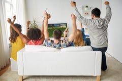 Vrienden met bier het letten op voetbal op TV thuis royalty-vrije stock afbeelding