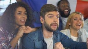 Vrienden met Franse vlag ondersteunend nationaal sportenteam in bar, kampioenschap stock videobeelden