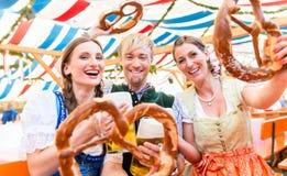 Vrienden met reuzepretzels in Beierse biertent stock fotografie