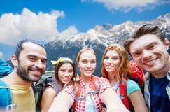 Vrienden met rugzak die selfie over bergen nemen stock foto