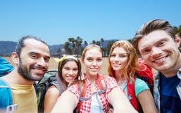 Vrienden met rugzak die selfie over strand nemen stock foto's