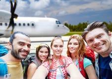 Vrienden met rugzak die selfie over vliegtuig nemen royalty-vrije stock fotografie