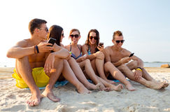 Vrienden met smartphones op strand Stock Afbeeldingen