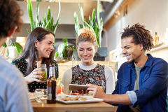Vrienden met tabletpc, dranken en voedsel bij bar stock foto's