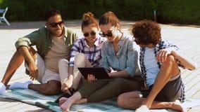 Vrienden met tabletpc op houten terras in de zomer stock video