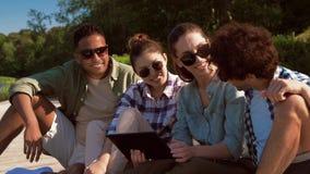 Vrienden met tabletpc op pijler bij meer of rivier stock videobeelden