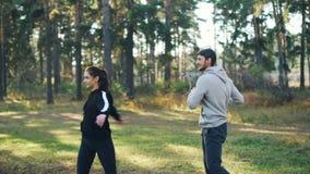 Vrienden mooi meisje en gebaarde kerel die sporten doen, en in openlucht in park in de herfst glimlachen spreken Aantrekkelijke j stock videobeelden