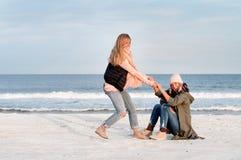 Vrienden op het strand in de herfst Stock Afbeeldingen