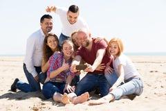 Vrienden op het strand worden gefotografeerd dat Stock Foto's