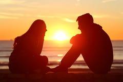Vrienden of paar van tienerjaren die bij zonsondergang onder ogen zien Stock Fotografie