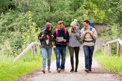 Vrienden of reizigers die met rugzakken en kaart wandelen stock afbeeldingen