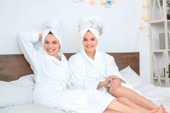 Vrienden samen thuis in de schoonheidsverzorgingzitting die van badrobes blije camera kijken royalty-vrije stock foto