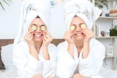 Vrienden samen thuis in de schoonheidsverzorgingzitting die van badrobes ogen behandelen met komkommerstukken toothy glimlachen stock fotografie