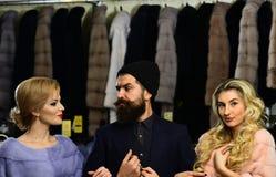 Vrienden in winkel: dames en heer in dure overjassen royalty-vrije stock fotografie