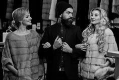 Vrienden in winkel: dames en heer in dure overjassen stock foto's