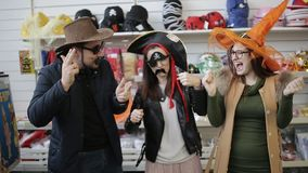 Vrienden in winkelcomplex in grappige Carnaval-hoeden die en pret hebben dansen stock videobeelden