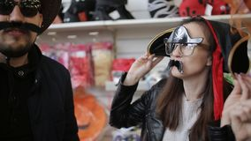 Vrienden in winkelcomplex in grappige Carnaval-hoeden die en pret hebben dansen stock footage