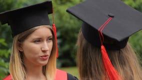 Vriendengediplomeerden die in park dichtbij universiteit na graduatieceremonie spreken stock footage