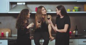 Vriendentijd voor een groep dames in de moderne keuken hebben zij een gesprek het drinken wijn en het voelen goed stock footage
