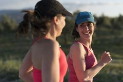 Vriendenvrouw die en in openlucht in werking gestelde opleiding in spri spreken glimlachen stock foto